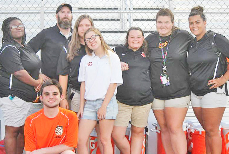 Kerry Clewell with BCHS student aides who work the sidelines of various sports ranging from football to volleyball. He is joined here by, from left, Kayla Jones, Adam Arnette (foreground), Nina Quezada, Tessa Jones, Lindsay Howard, Grace Girby, and Allie Flowers.