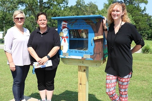 The newest Free Little Library is stationed outside the Dollar General Store in Perdido. Built by Evan White, the mini library was painted in a Dr. Seuss theme by local artist Nancy Self. Unveiling the new library are, from left, Nancy Self, Store Manager April Kelly, and Joanna Bailey, Director of the Bay Minette Public Library.