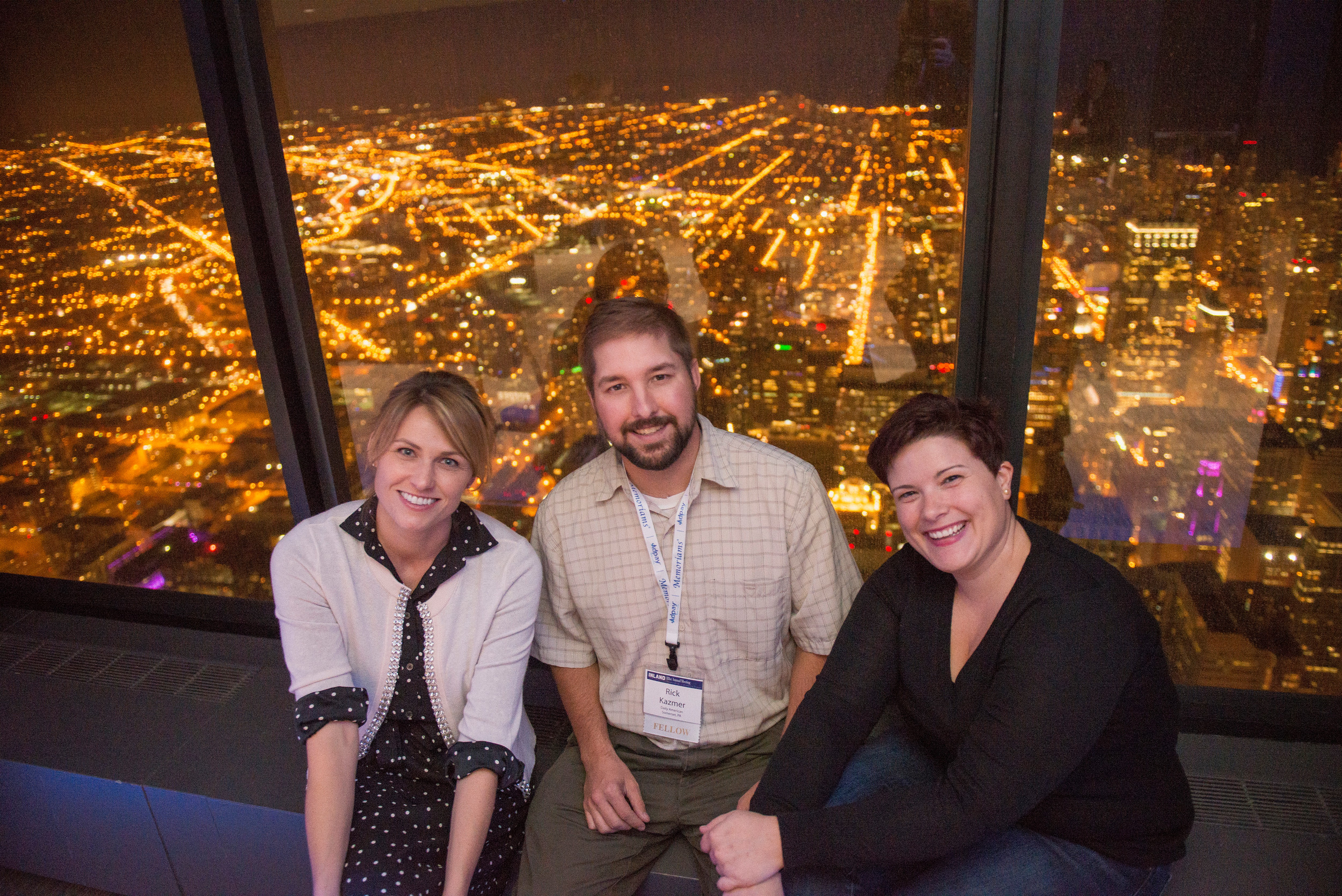 Three of Inland's new Fellows pose 99 stories above Chicago at the Annual Meeting reception in the Willis Tower. From left, Kelli Scott of the Wenatchee (Wash.) World, Rick Kazmer of the Daily American in Somerset, Pa., and Alessia Alaimo of Wick Communications.