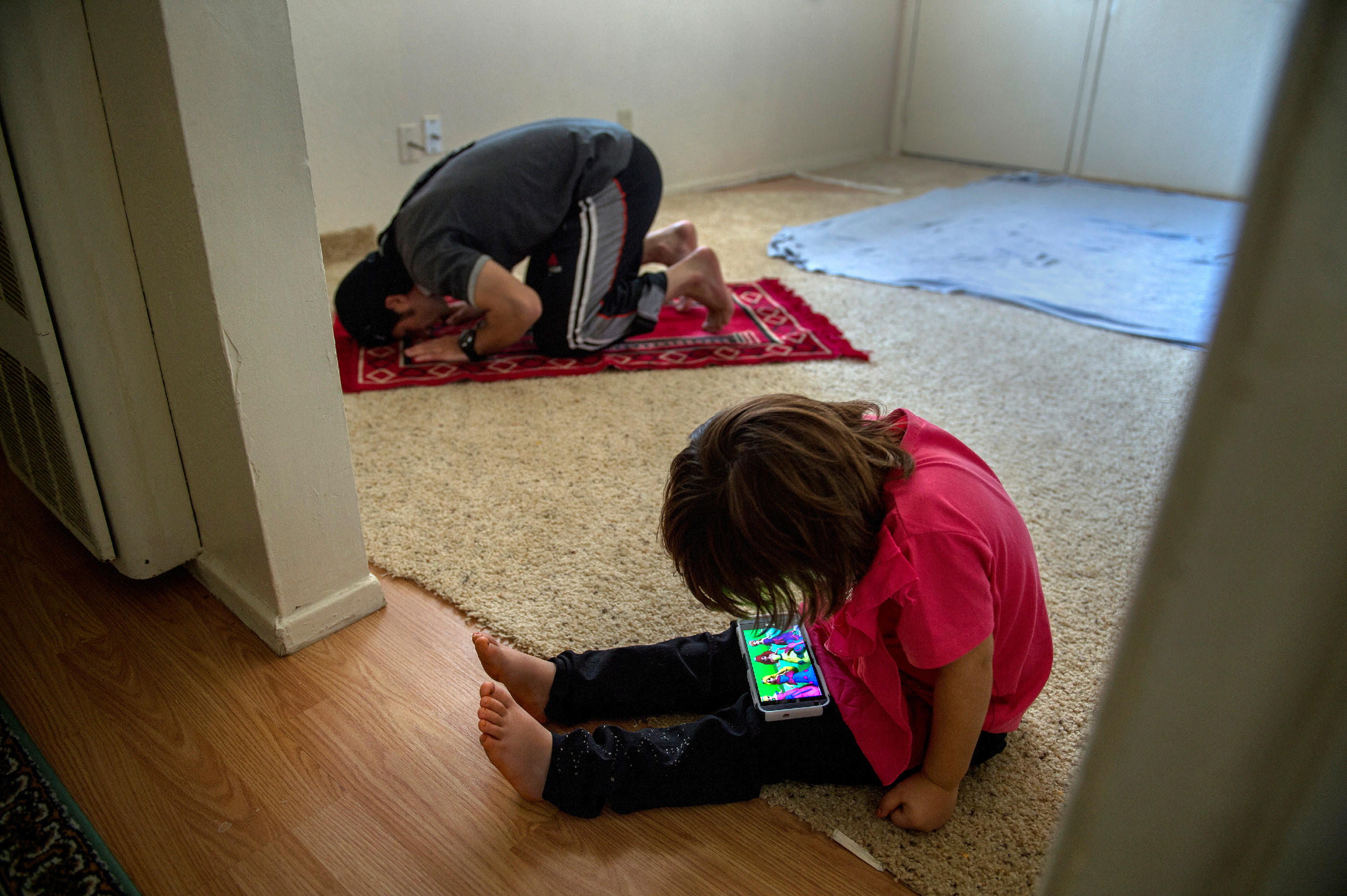 As Abdul Farhad Ghafoori says his prayers, his daughter, Kayinat, 4, watches American cartoons on his cellphone. Without toys available, he handed her the phone to calm her after her mother left for ESL class. Finding affordable day care is a struggle for the refugees, whose wives are required to take ESL classes.