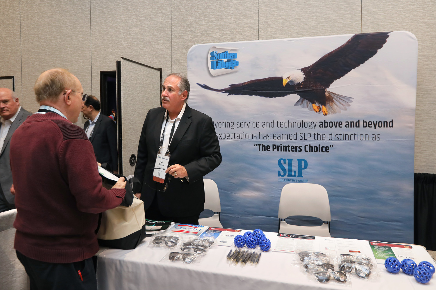 Gil Green, regional manager for Southern Lithoplate, talks with a Mega-Conference attendee in the Exhibit Hall. The 2018 Mega-Conference attracted a record number of vendors.