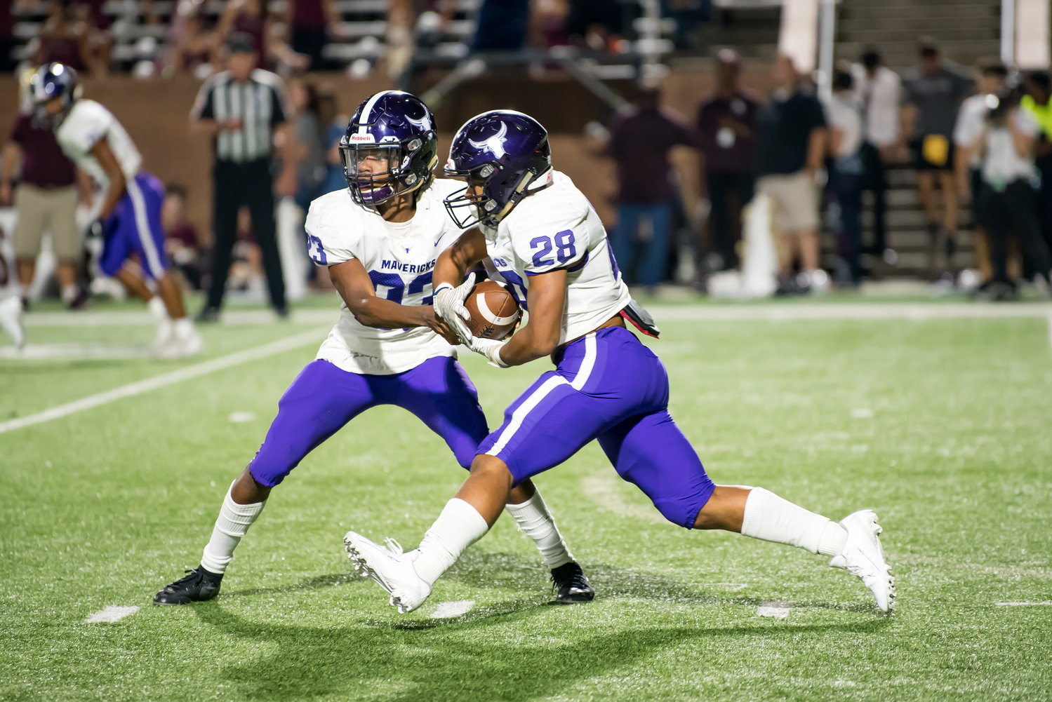 Morton Ranch quarterback Jaymarcus Wilson (23) hands off to running back Devin Winfield during a game against Cinco Ranch on Oct. 4 at Legacy Stadium.