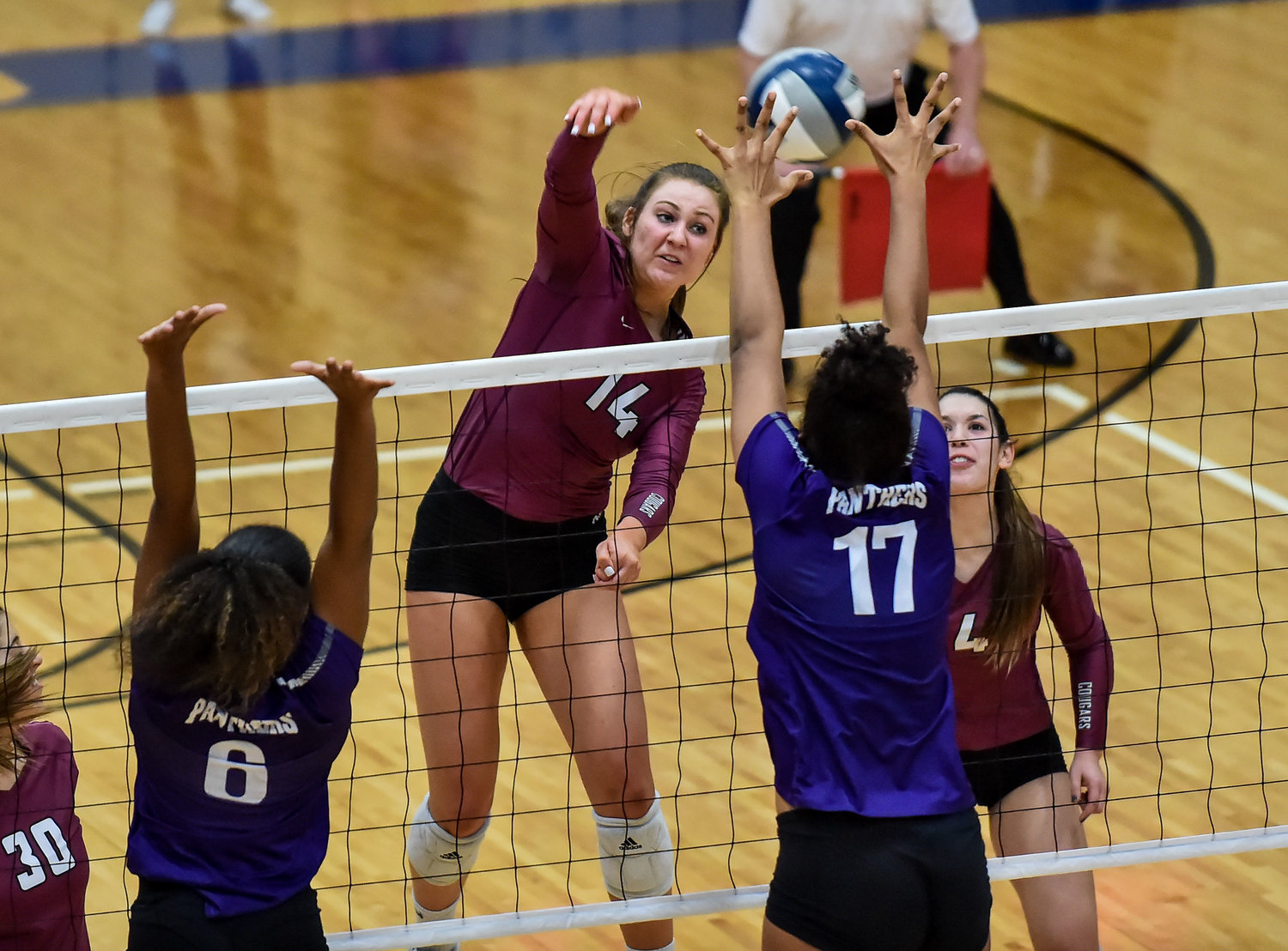 Katy Tx. Nov. 12, 2019: Cinco Ranch's Danyle Courtley (14) delivers the shot as Ridge Points Alexis Roberson (17) attempts the block during the Regional Quarter Final High School Volleyball playoff match between Cinco Ranch and Ridge Point at Wheeler Field House.  (Photo by Mark Goodman / Katy Times)
