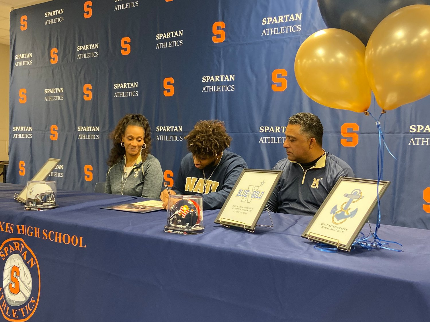 Seven Lakes senior defensive lineman Jaymian Simon signs his national letter of intent as his parents mother Shawnie and father Johnny look on during Early Signing Day on Dec. 18 at Seven Lakes High.