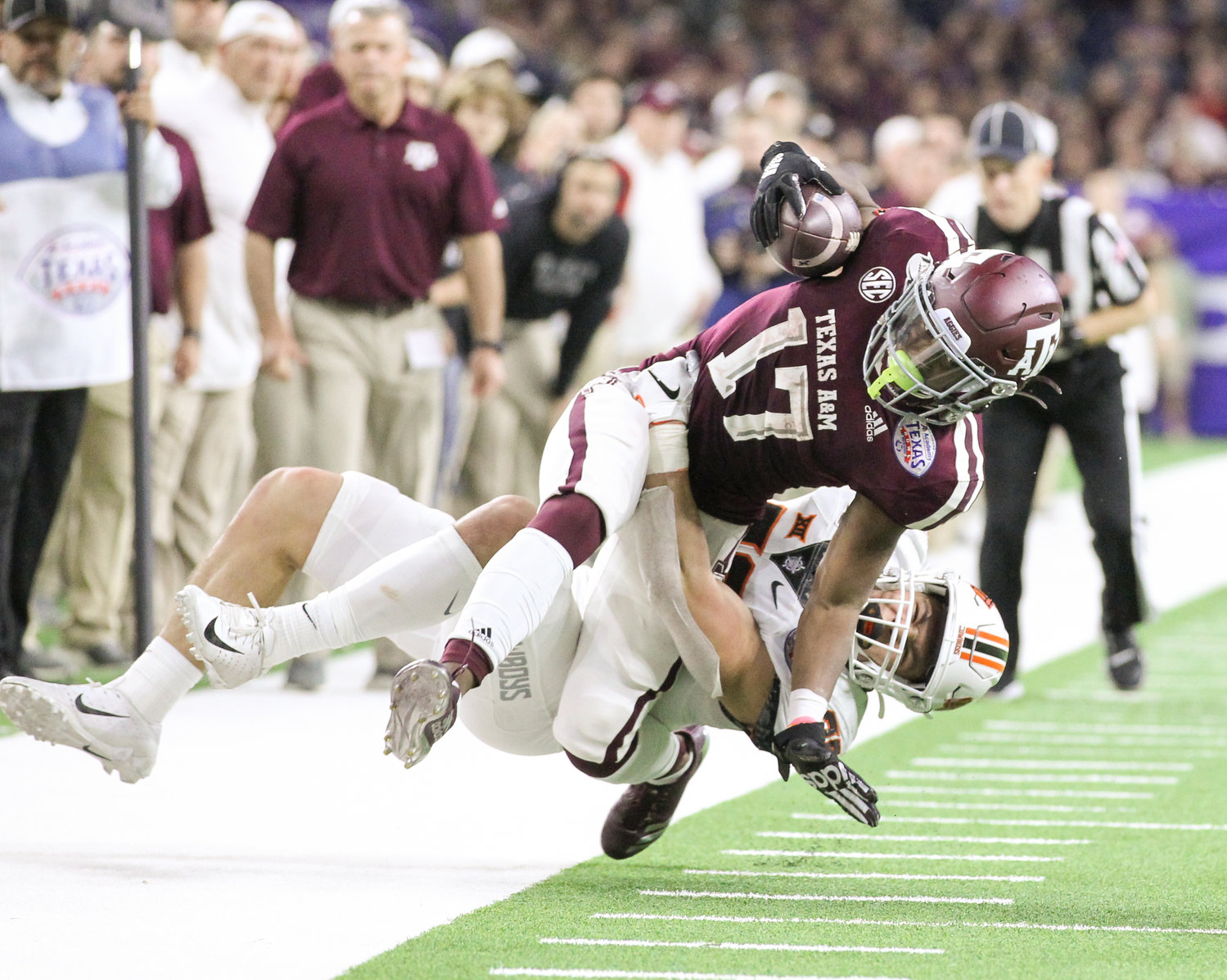Texas A&M Aggies wide receiver Ainias Smith (17) is tackled by Oklahoma State Cowboys safety Malcolm Rodriguez (20) during an NCAA football bowl game between Texas A&M and Oklahoma State at NRG Stadium in Houston, Texas, on Dec. 27, 2019.