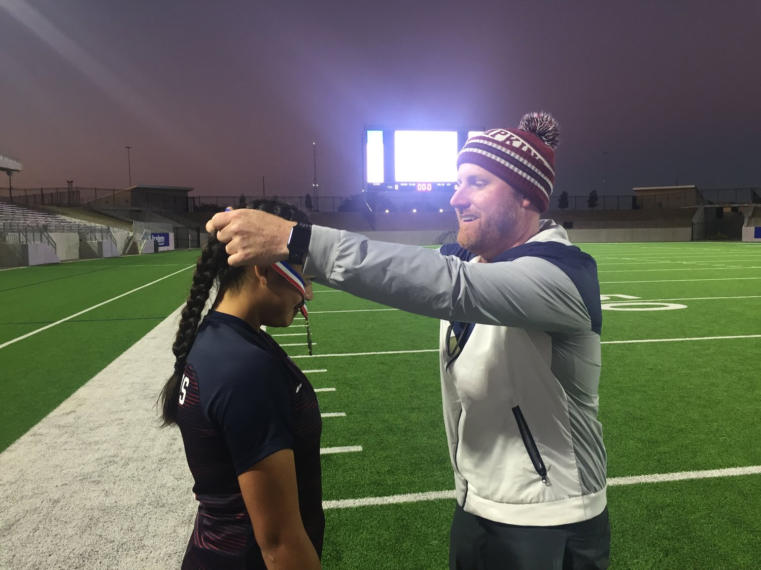 Tompkins girls soccer coach Jarrett Shipman, right, places a medal around then-junior forward Felicia Hernandez after the Falcons' championship win in the Falcon Bracket of the I-10 Shootout at Legacy Stadium last year.
