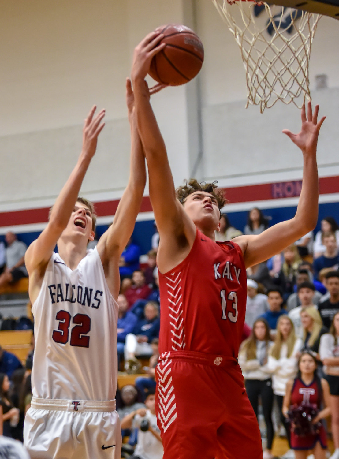 Katy Tx. Jan. 10, 2019: Katy's Casper Belaiter (13) and Tompkins Bryson Morehead (32) go up for the rebound during a district basketball game between Tompkins Falcons and Katy Tigers at Tompkins HS.  (Photo by Mark Goodman / Katy Times)