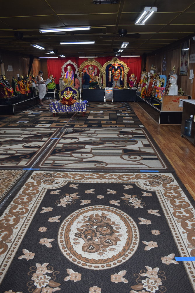 Hindu worshipers pray while a monk reads at Sai Durga Shiva Vishnu Mandir. The floor of the temple, which usually has more followers during prayer times, is marked with blue painters tape to ensure worshipers can maintain a safe social distance from one another.