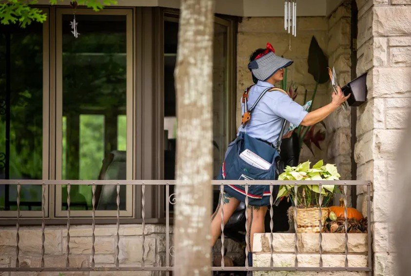U.S. Postal Service employee Sweetie Dionne delivers mail on her route in Austin on April 6. The USPS has warned Texas officials that some ballots cast by mail may not arrive in time to be counted for the Nov. 3 election.