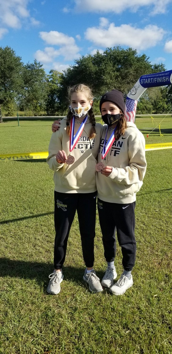 Jordan High freshmen Addison Sutton, left, and Beatriz Laepple qualified for regionals after finishing fifth and 10th, respectively, at the District 19-5A cross country championships Thursday morning in Katy.
