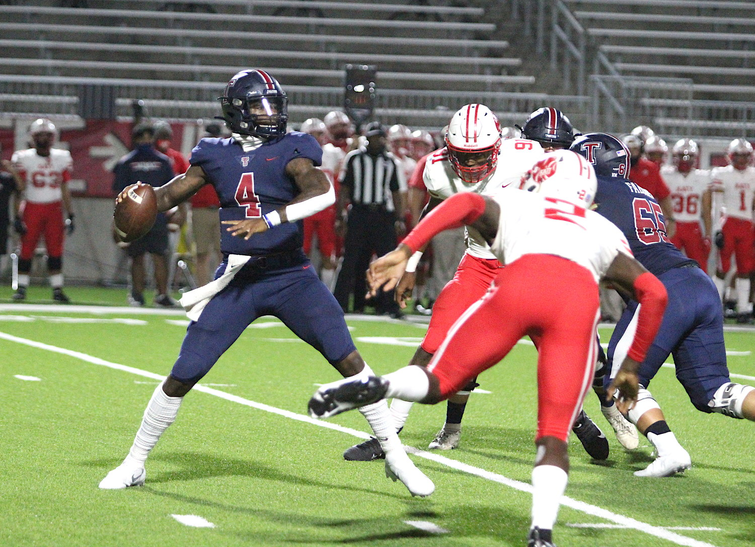 Tompkins senior quarterback Jalen Milroe (4) stands tall in the pocket as Katy junior defensive end Malick Sylla attempts to rush during the Falcons' 24-19 win over Katy on Nov. 5 at Legacy Stadium.
