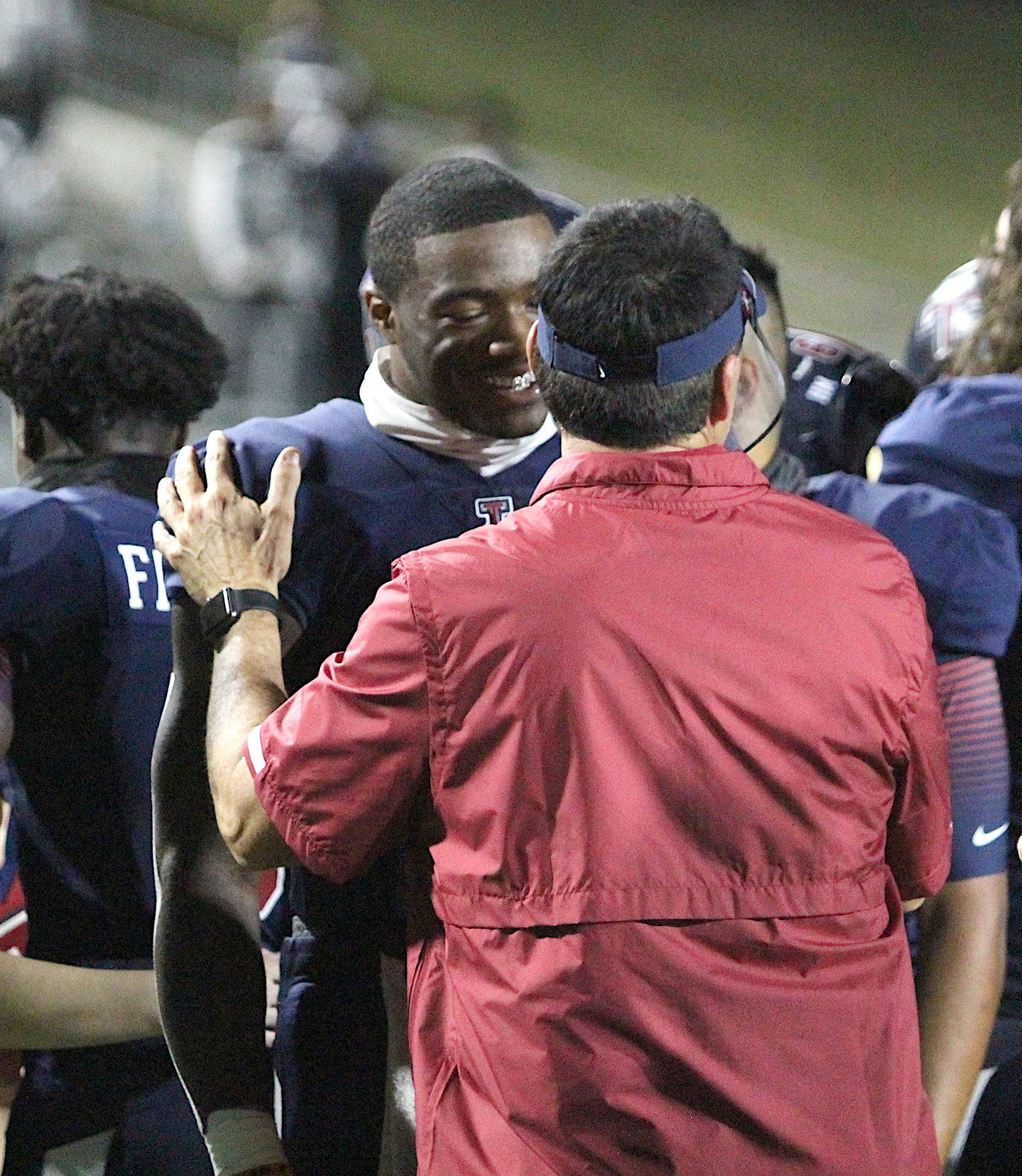 Tompkins senior quarterback Jalen Milroe and Tompkins head coach Todd McVey share a congratulatory moment after the Falcons' 24-19 win over Katy on Nov. 5 at Legacy Stadium.