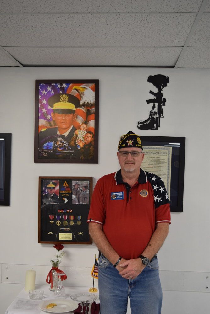 American Legion Post 164 Commander Jim McGuire poses in front of a commemorative wall honoring Second Lieutenant Jonathan D. Rozier, the post's namesake.