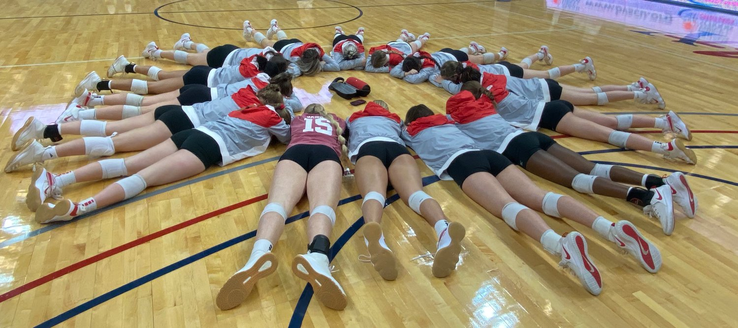 Katy High volleyball players take some quiet time together to meditate prior to their Class 6A regional semifinal against Clear Springs on Tuesday at the Merrell Center.