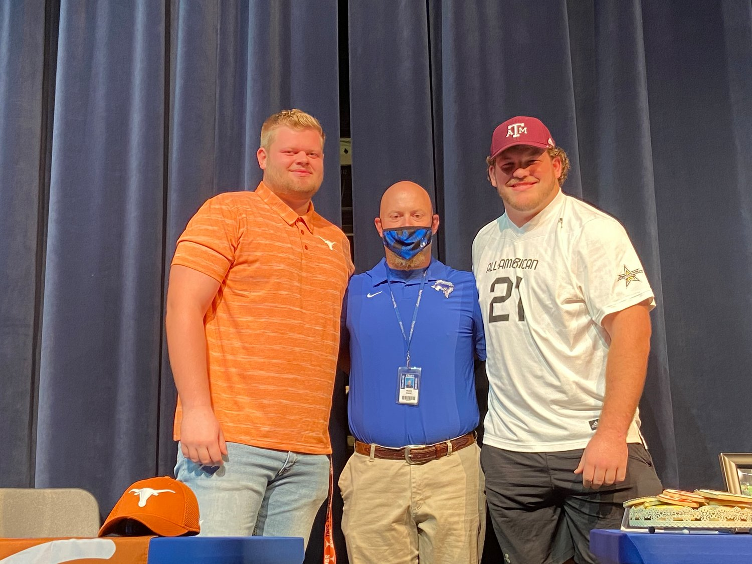 Taylor High senior offensive tackle and Texas signee Hayden Conner, left, and senior offensive guard and Texas A&M signee Bryce Foster, right, pose for a photo with offensive line coach Travis Sharp during their signing ceremony Friday at the performing arts center at Taylor High.