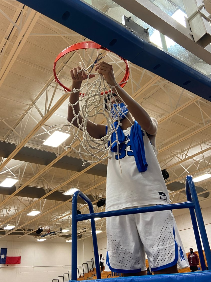Taylor sophomore center Elijah Melchiorre cuts down a string from the net in celebration of the Mustangs' 69-39 win over Seven Lakes on Feb. 5 that won Taylor its first district championship in 26 years.