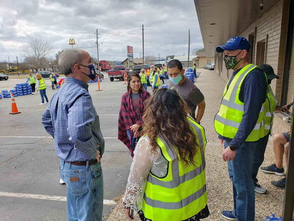 State Representative Mike Schofield (left in blue) speaks with volunteers and staff at Katy Christian Ministries where he helped distribute cases of water for multiple days as his constituents worked to recover from Winter Storm Uri.