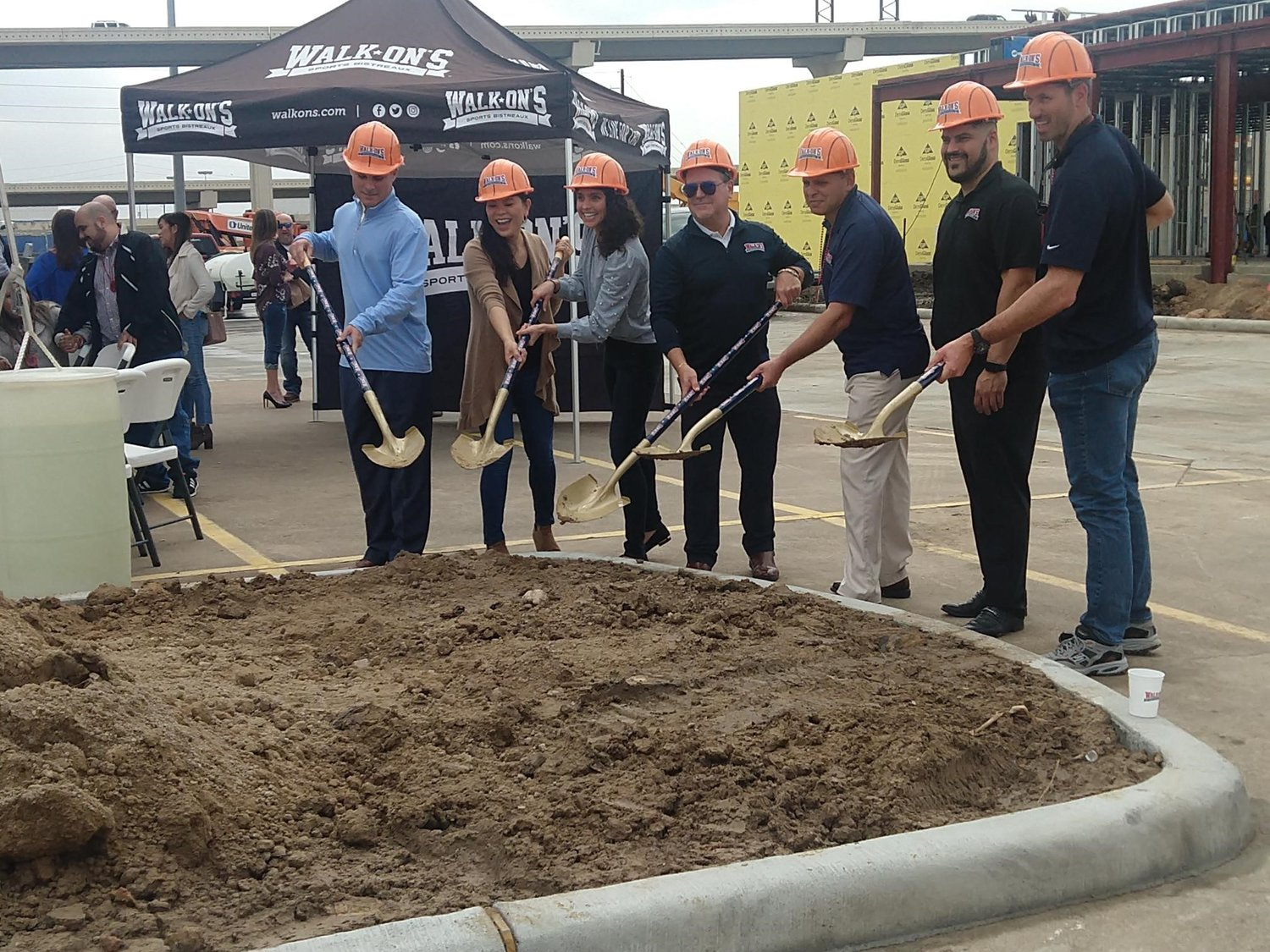Franchisee Paul Alfonso (khaki pants) and his team participate in the ground-breaking ceremony for Walk-On's Sports Bistreaux in the northeast corner of the intersection of I-10 and The Grand Parkway in Katy on Friday, Feb. 26.