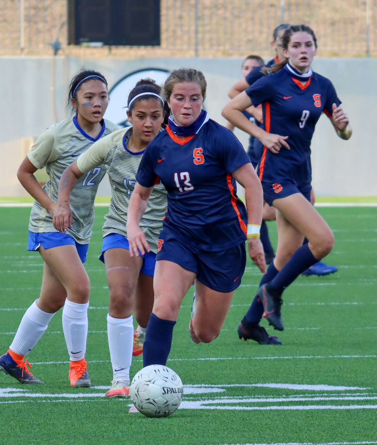Seven Lakes senior midfielder Phoebe Harpole moves downfield ahead of Elkins defenders during the Spartans' 7-0 Class 6A bi-district playoff win on Friday, March 26, at Legacy Stadium.