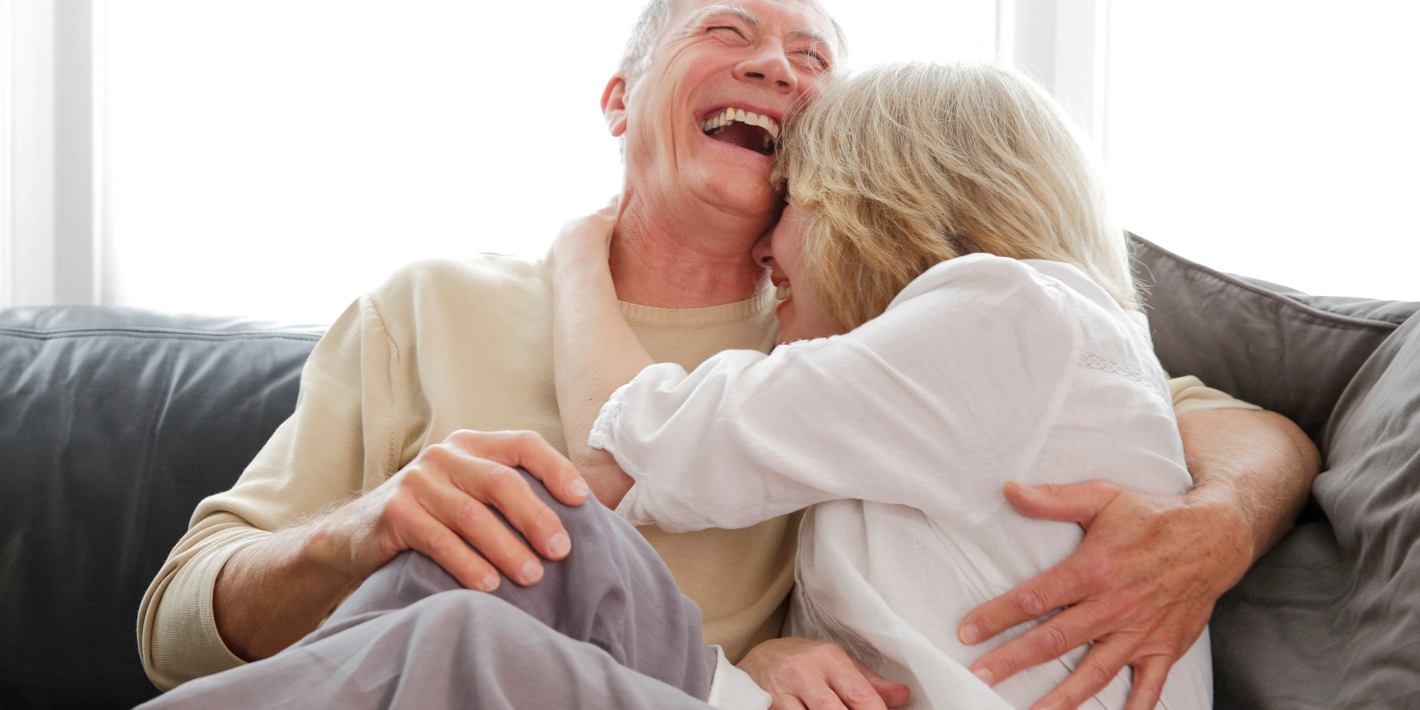 Mature couple laughing and cuddling.