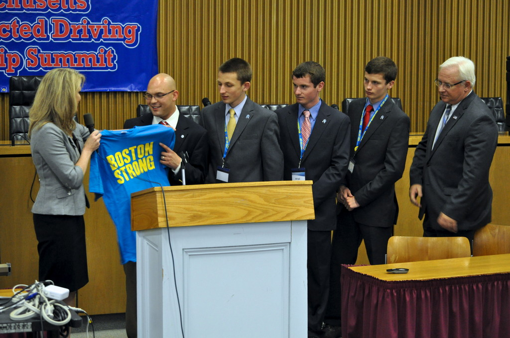 "National AT&T spokesman and texting accident survivor Wil Craig (pictured second in from the left) accepts a ""Boston Strong"" T-shirt at AT&T's Distracted Driving Summit from AT&T New England President Patricia Jacobs. The even was organized by Seekonk High School triplets Tim, Brian, and Matt Salit (pictured left to right, respectively) and Essex County District Attorney Jonathan Blodgett (far right). The summit was held at the Massachusetts State House."
