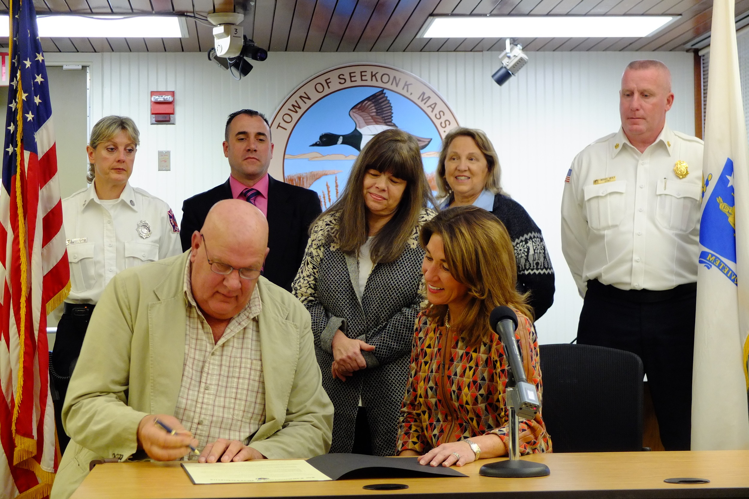 Seekonk Signs Community Compact: Selectman David Perry and Lt. Governor Karyn Polito sign the Community Compact as Rehoboth Town Administrator Helen Dennen looks on.  Standing behind them are (L to R) Seekonk FIre Capt. Sandra Miller, Seekonk Selectman Nelson Almeida, Seekonk Selectwoman Michelle Hines, and Seekonk Fire Chief Michael Healy.