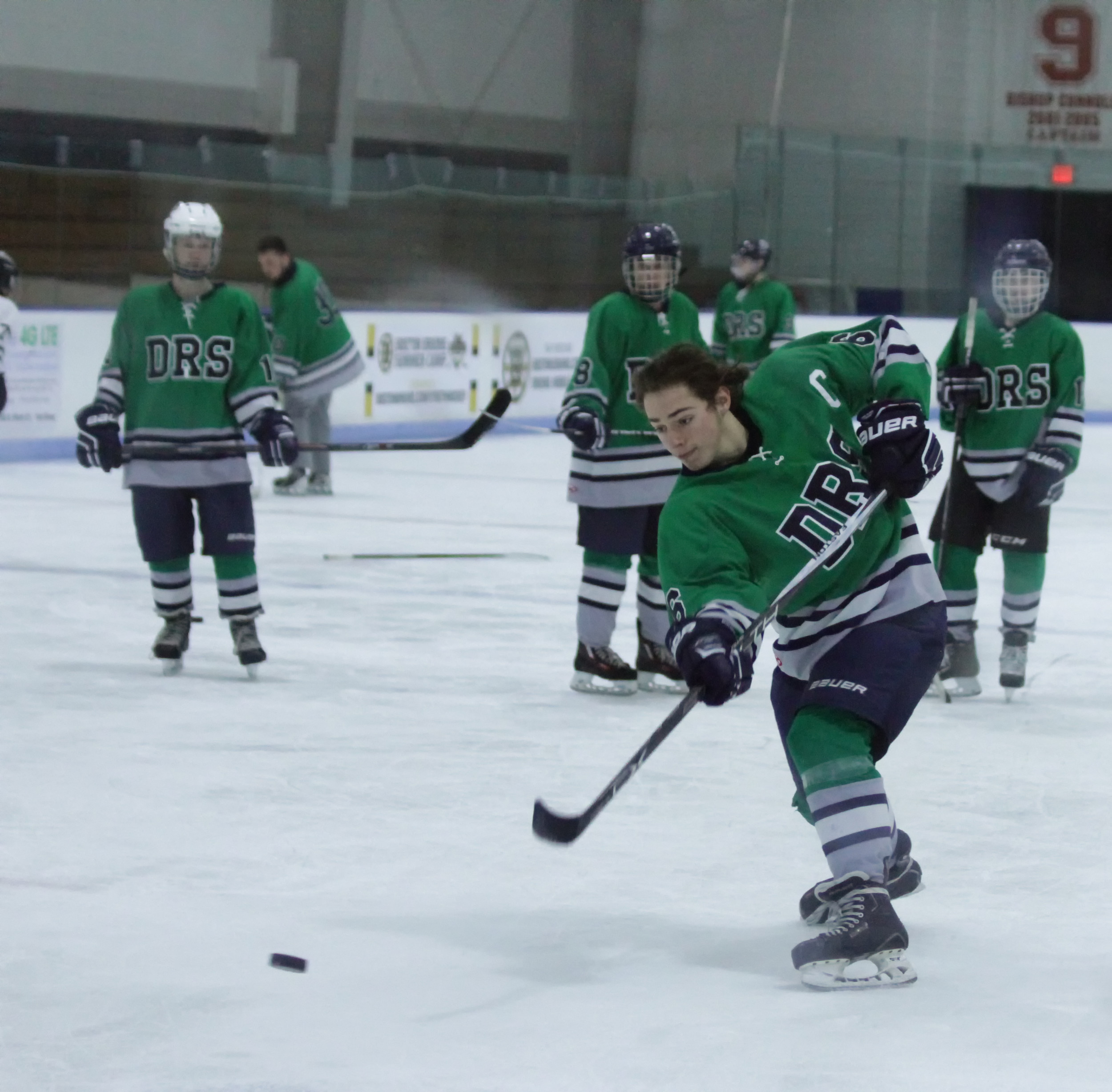 "DHS co-captain, Chris Fernandez, powers through a slap shot as he competes with teammates for the ""hardest shot""."