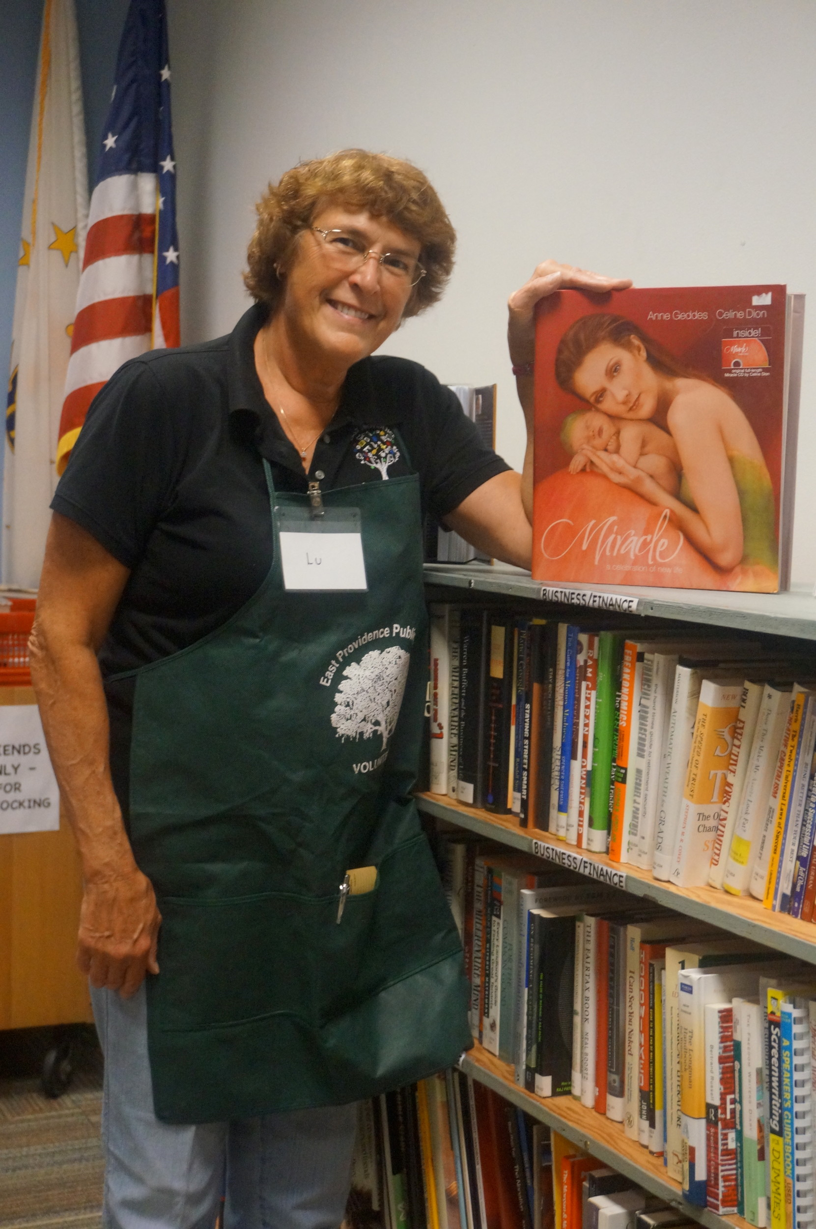 Lu Rodrigues stocks the book shelves for the Friends of the Library's Spring Book Sale at Weaver Library April 20-23.