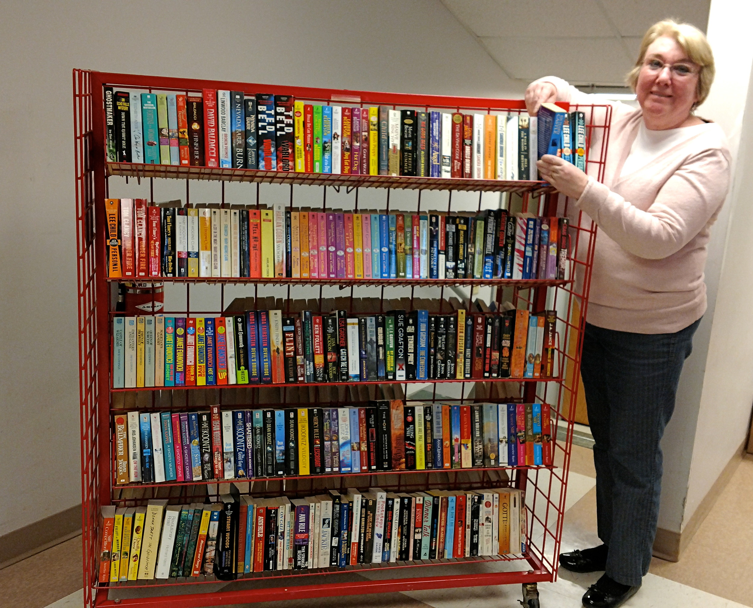 Volunteer Cheryl Muth arranges paperback novels on book cart designed to be more user-friendly for patrons at the upcoming book sale.