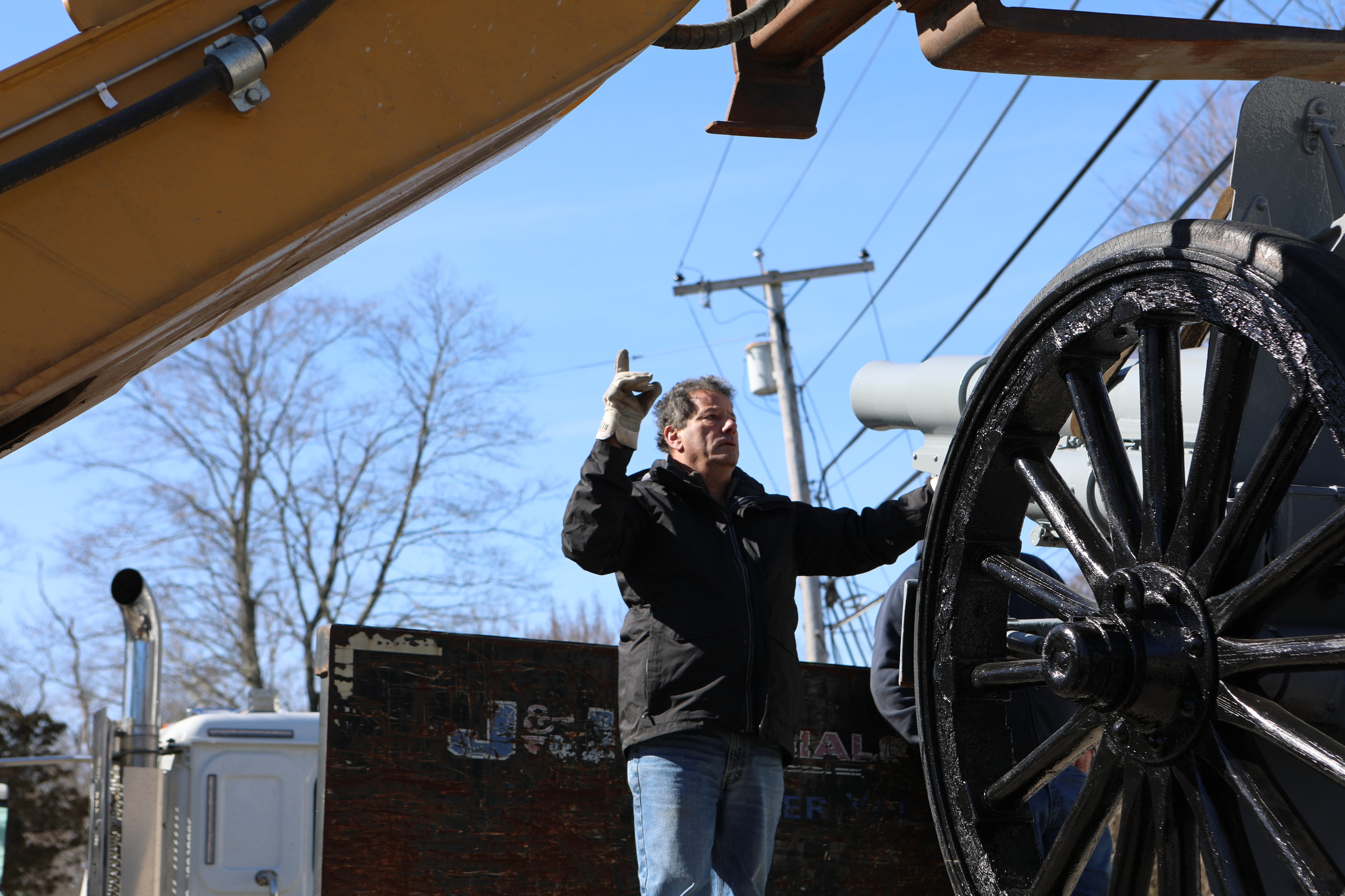 John Ferreira Sr. giving the forklift operator hand signals during the downloading of the cannon.
