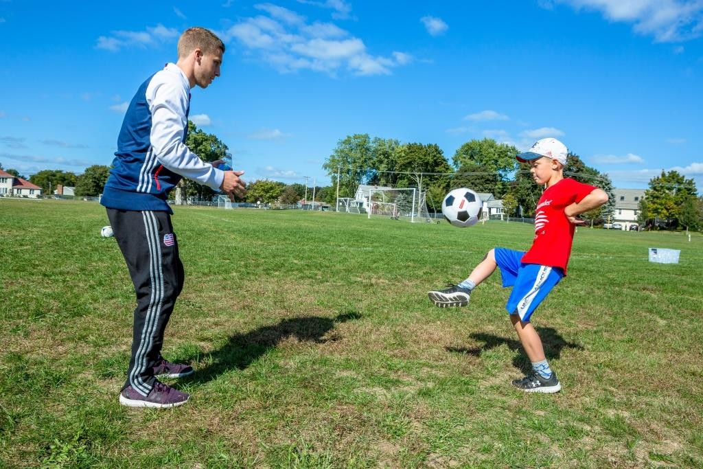 New England Revolution midfielder Scott Caldwell juggled the ball with 4th grader and Santander Soccer Scholars 2016 winner Camden Lander of Seekonk on the field at his elementary school.
