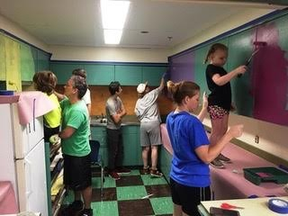 Pack 88 Cub Scouts (Rumford) and Troop 1 Boy Scouts (Seekonk) and their families paint cabinets in the art room at St. Margaret School. The Scouts are participating in the Boy Scouts of America Adopt-A School program