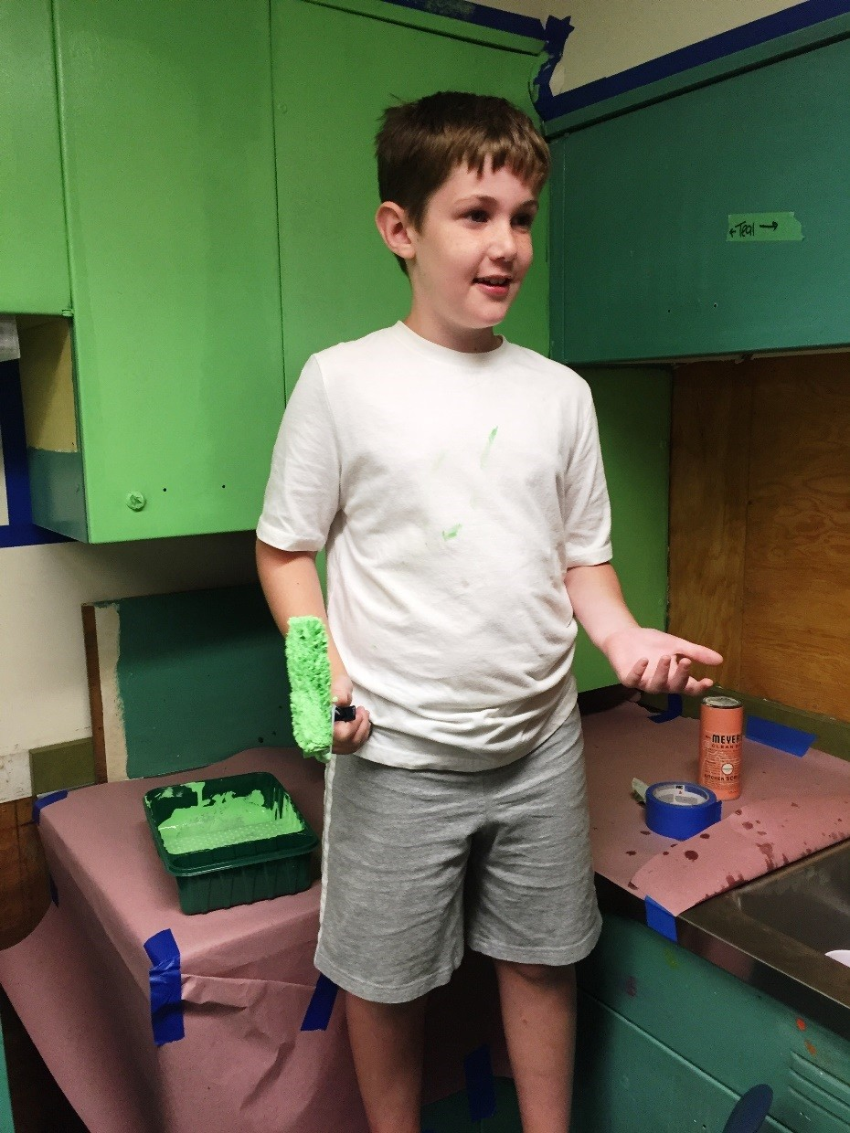 Slate Vandal, son of Pack 88 Cub Scout leader Chris Vandal, paints cabinets in the art room