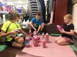 Pictured left to right: Alex Gries, Mason Doherty, and Addie Doherty sort and organize paint and other art supplies.