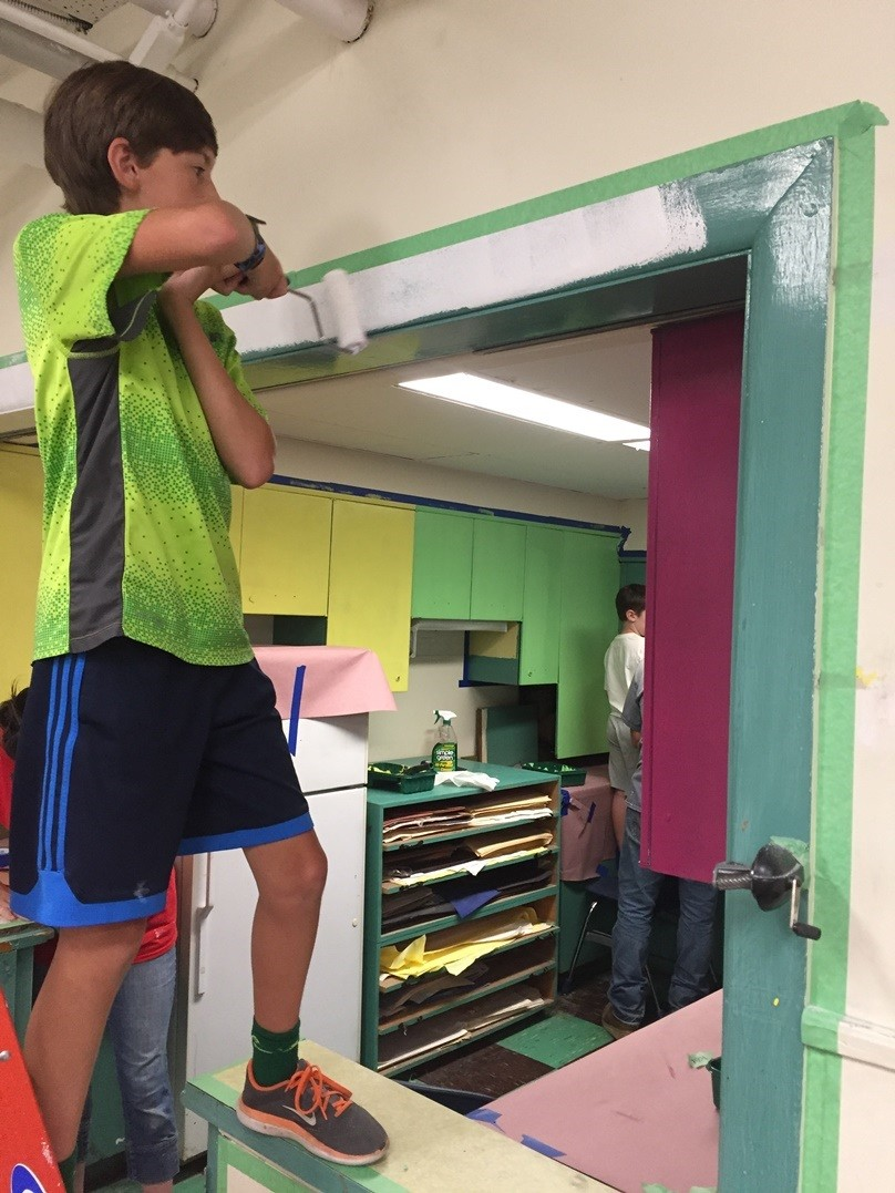 Jakob Gries paints trim in the art room at St. Margaret School.