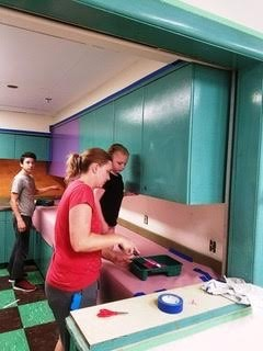 Matthew Lloyd, Pack 88 Committee Chairperson Michelle Gries, and Addie Doherty paint cabinets in the art room at St. Margaret School.