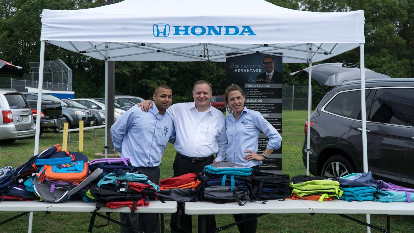 Herb Chambers Honda of Seekonk donated 200 free back-to-school backpacks filled with school supplies for kids grade K-5. Families lined up eagerly for the backpacks; above, employees of Herb Chambers prepare to hand them out. Scott Birtles (center) organized the giveaway.