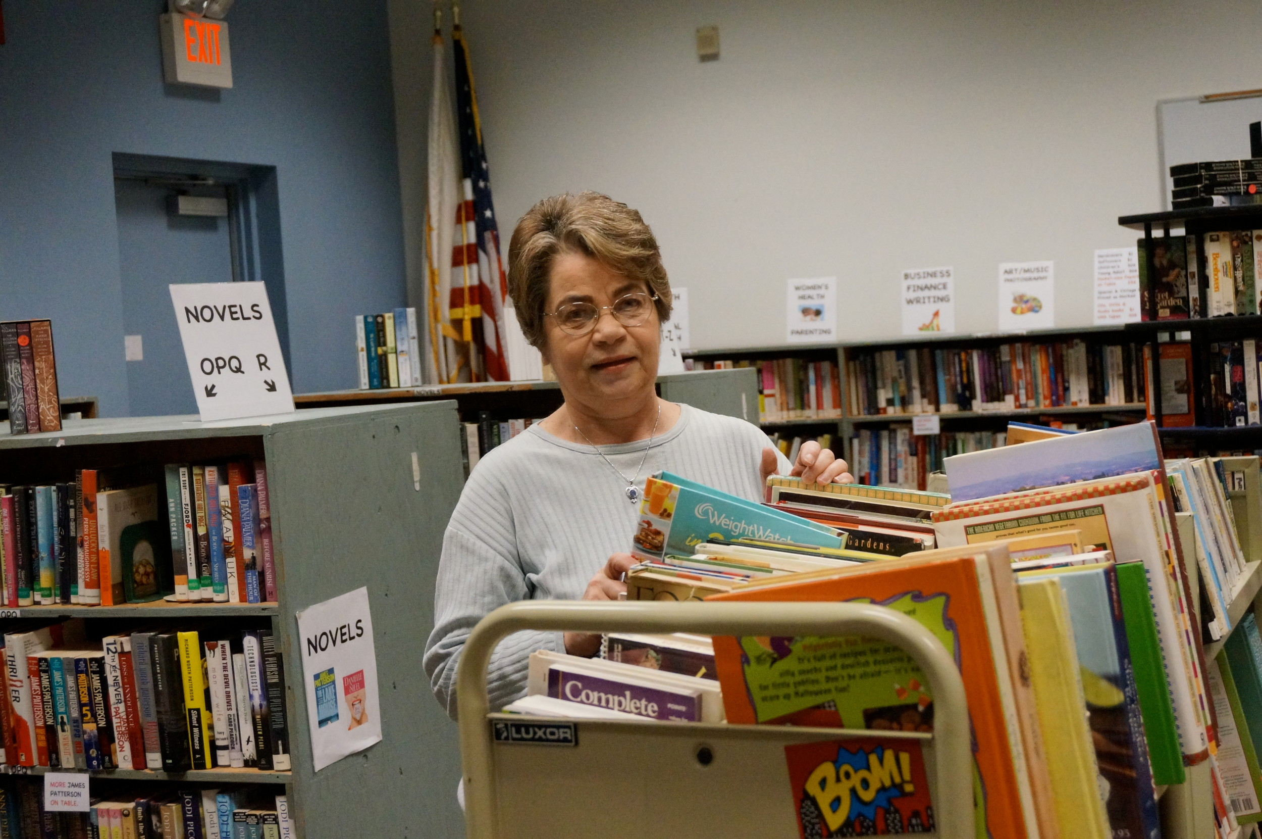 Ginnie Hogan, Friends volunteer, stocks some of the thousands of gently used books that will be selling at very reasonable prices at the Fall Book Sale at East Providence's Weaver Library October 19-22.