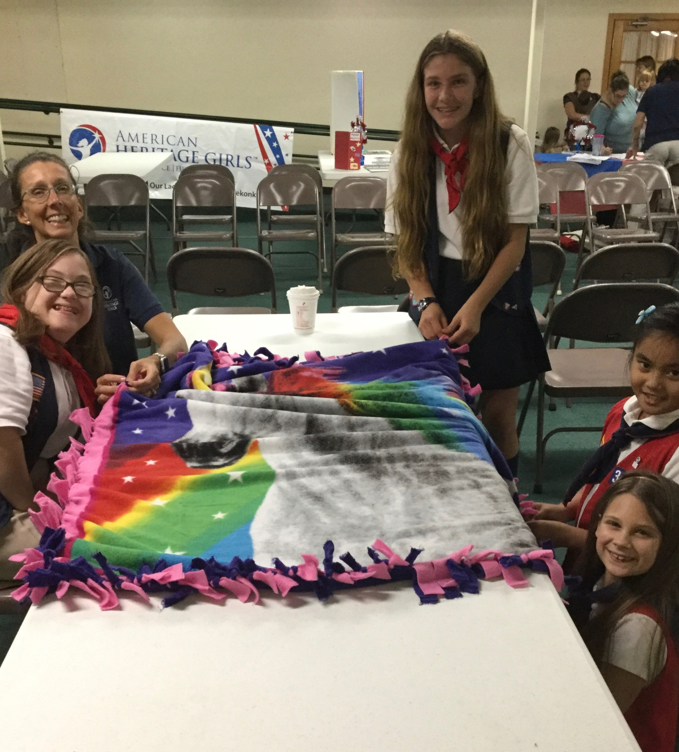 Explorer Leader Sharon Abbott helps Madison Burbank, Amanda Abbott (standing), Kriszel Dabi and Zoe Kuczewski complete a blanket.