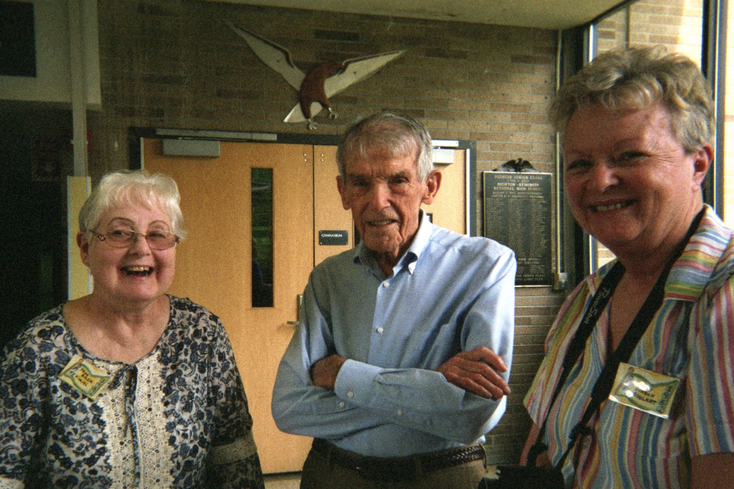 Surprise Visitor At School Tour:  The Reunion Committee kept secret that Dr. Joseph C. Harrington, the first principal, was there to greet his students, graduates almost to the day of 56 years ago.  Beneath the Falcon mascot by the gymnasium door, he is shown with Jane Boler Vinniti from Rehoboth and Nancy Binden Goulart from Dighton.  In the background is the plaque naming all 112 First Falcons.