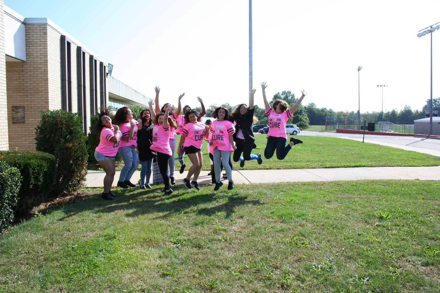 Juniors and seniors jumping to get ready for the walk for breast cancer.