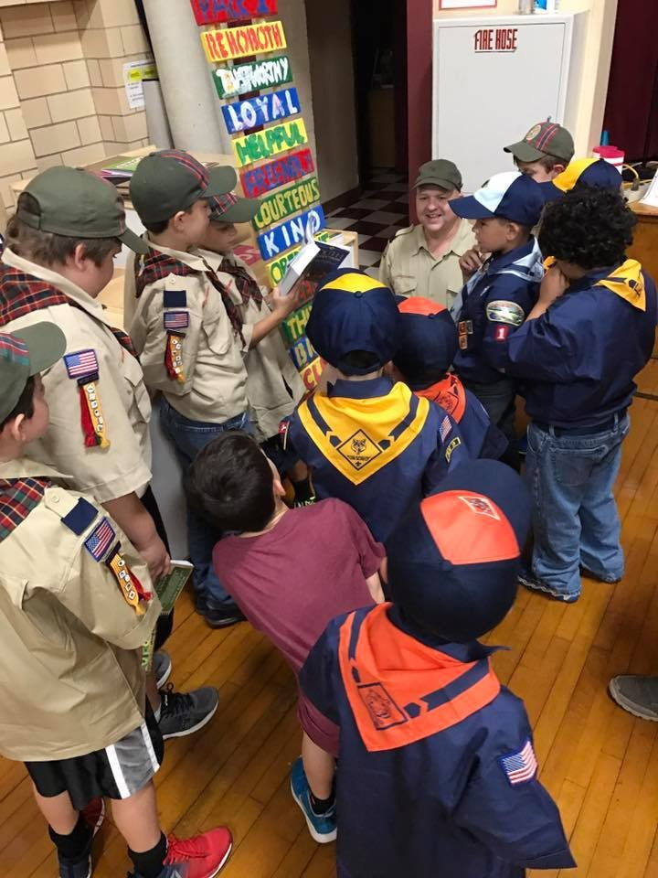 Arrow of Light leader Stephen Benjamin and his den teaching the younger Cub Scouts the Scout Law.