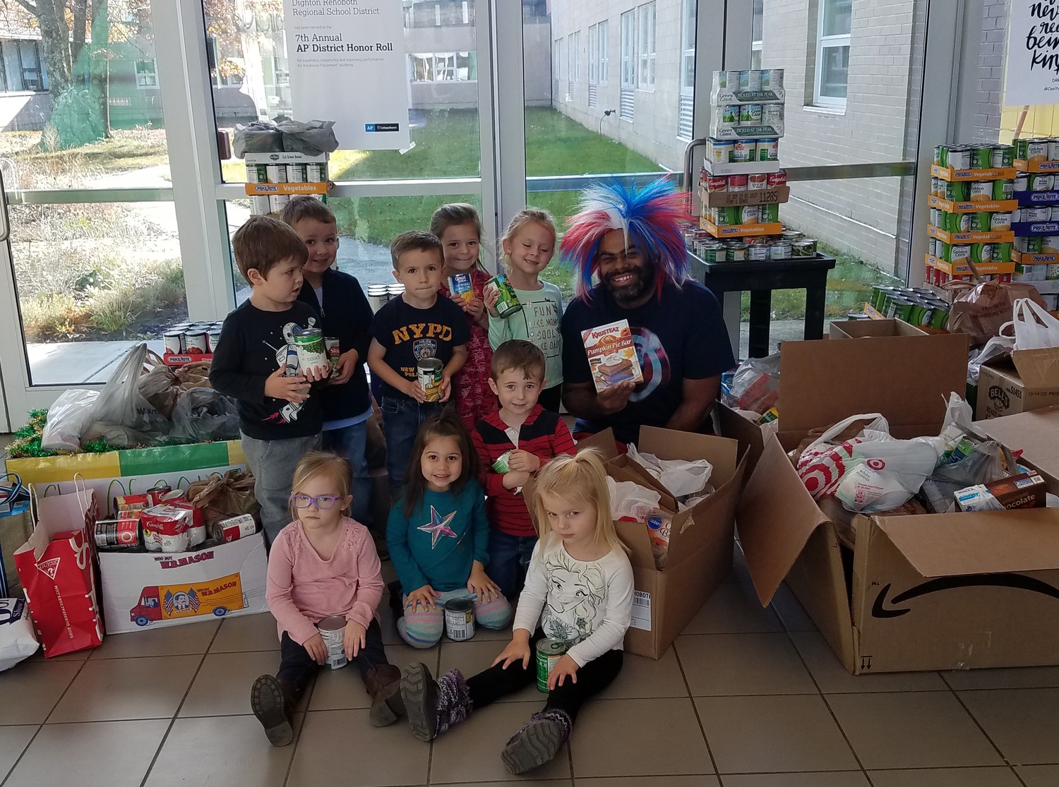 Preschoolers: preschooler and Dr. Bruce Tench (AP of high school) pose with some of the canned goods they brought in to support the communities.