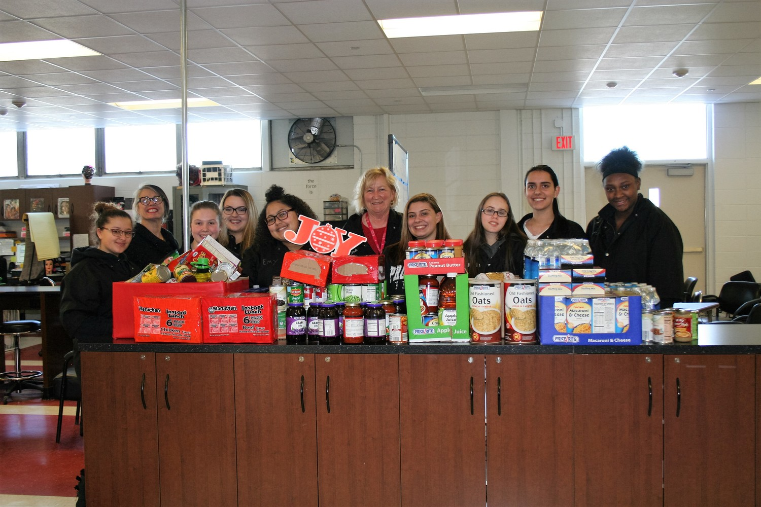 Winners of the canned food drive, Cosmetology, standing with their collection