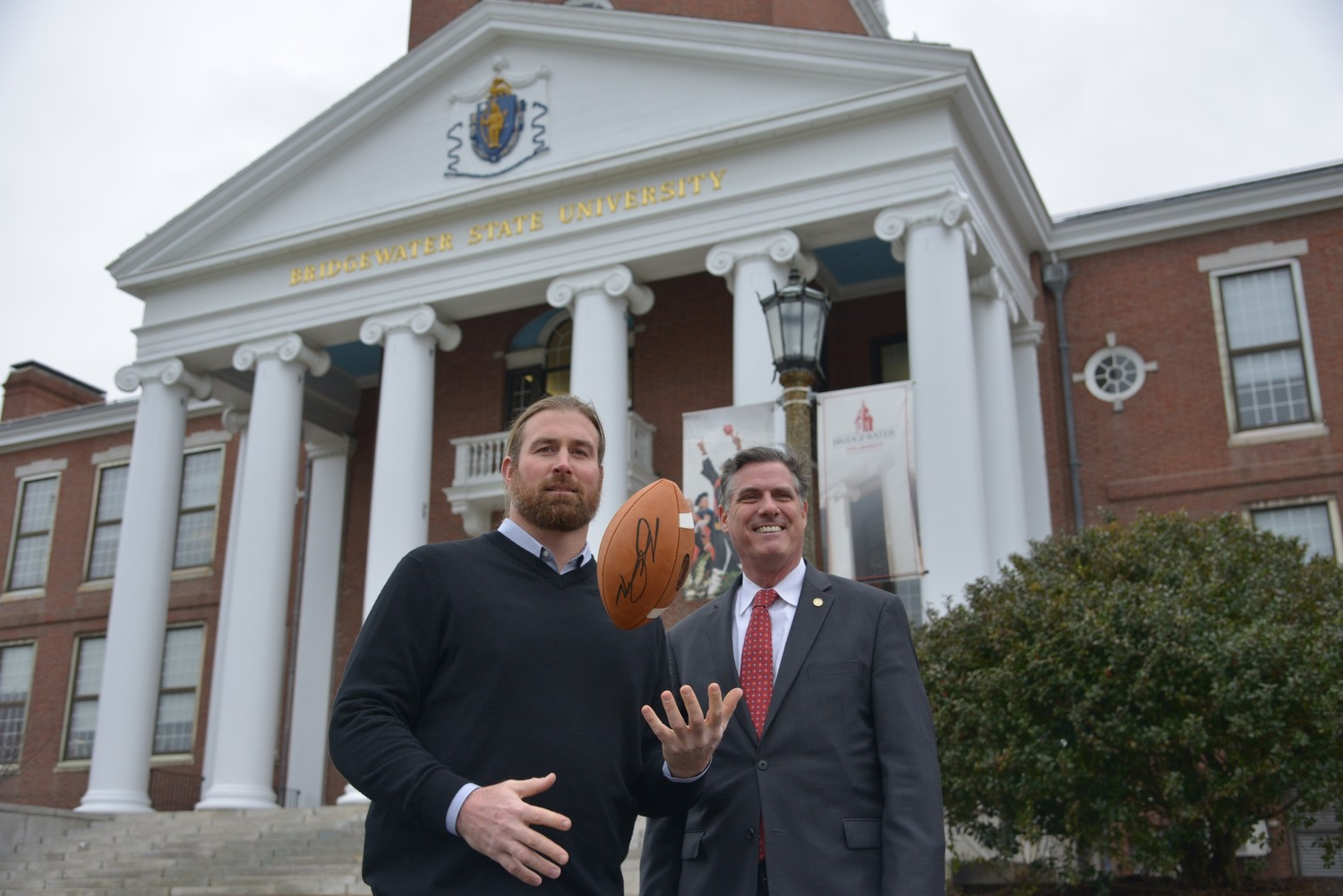 Former New England Patriot Matt Light and BSU President Frederick W. Clark Jr., Esq., discuss the Light Up BSU raffle organized through Lighthouse Raffles.