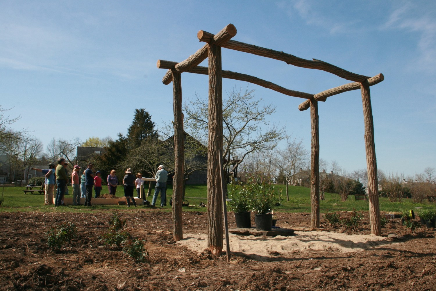 Volunteer gardeners gather behind the installed arbor as they listen to directions from Little Compton garden designer John Gwynne.