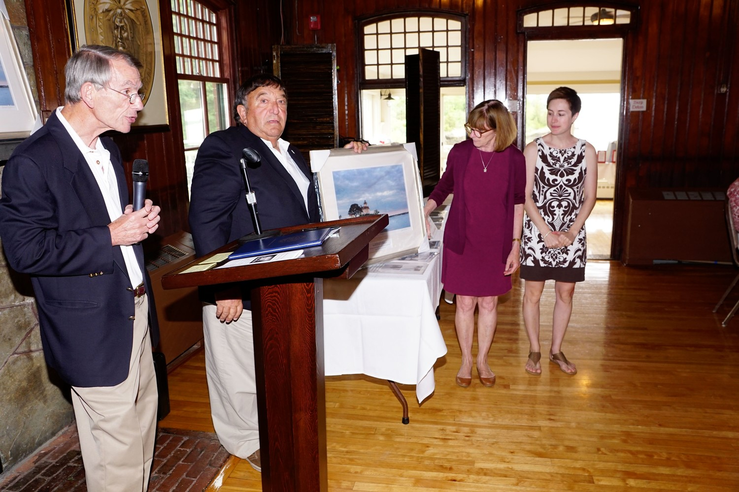 Nate Chace, Director of Development, and Joseph Estrella, Chair of Friends of Pomham Rocks Lighthouse, present a framed print of the Lighthouse to Roberta Randall and Katy Pomplun of Rhode Island Historical Preservation and Heritage Commission.
