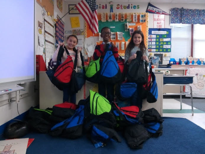 We've Got Your Back(pack): Mrs. Hopkins's  students loading the backpacks for delivery.