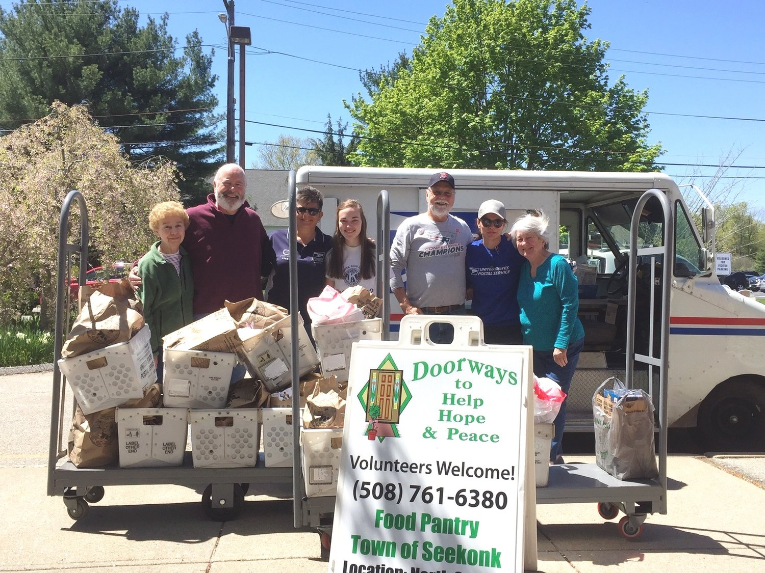 Seekonk Letter Carriers and volunteers from Doorways Food Pantry pose with some of the tons of food donated by postal patrons during the food drive on May 11.