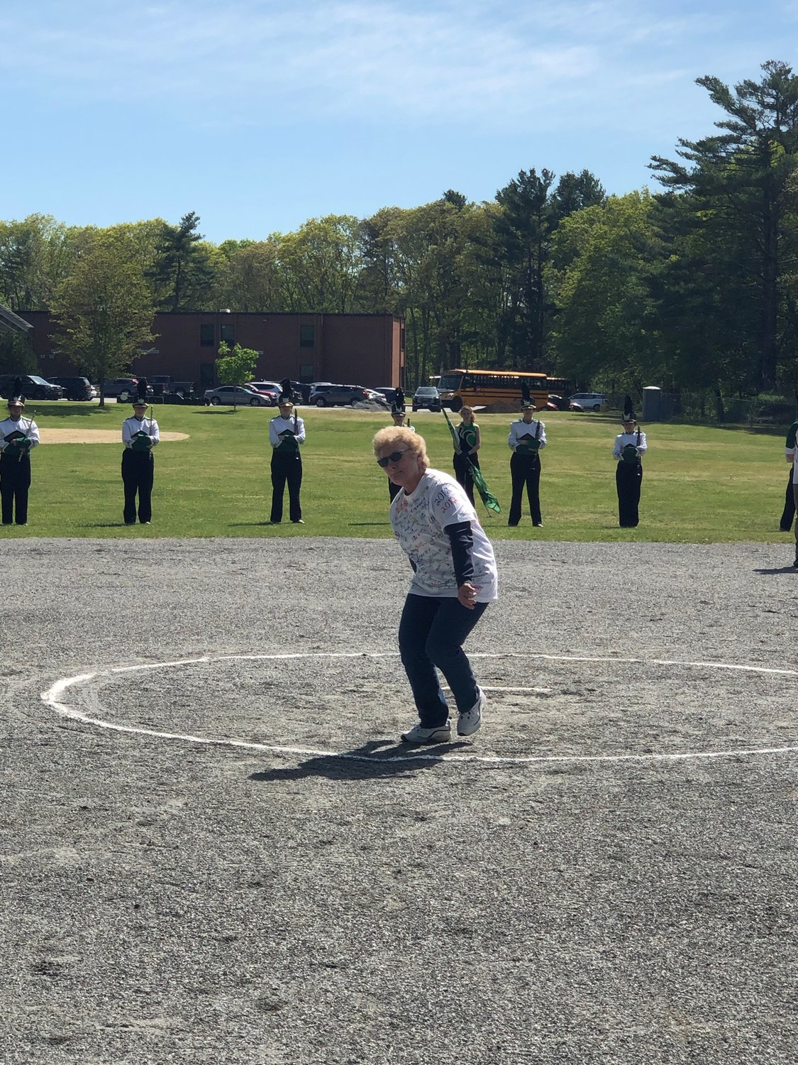 First Lady Raiders Softball Coach Liz Chellel throws a ceremonial first pitch.